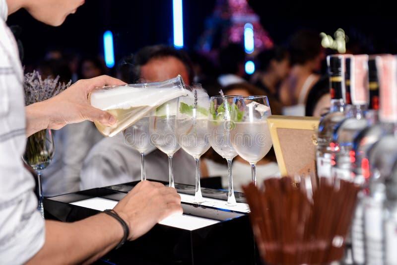 Фото руки бармена держа бутылку и лить воду из ее в событии партии стоковые изображения
