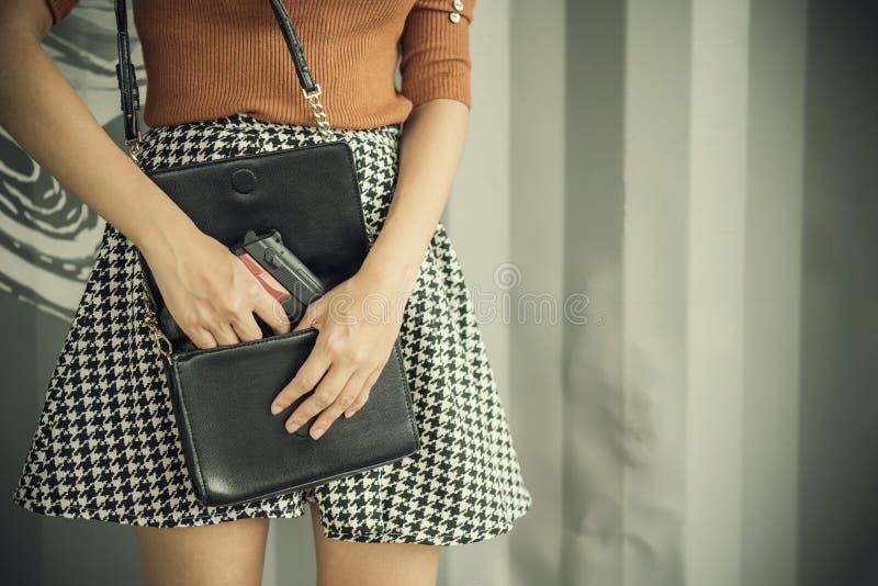 Фото руки молодой женщины вытягивая пистолет из ее сумки стоковые фото