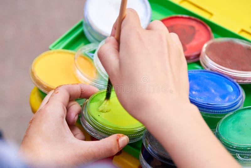Фото руки с щеткой, трубок краски, процесса чертежа стоковое фото