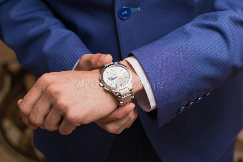 Фото свадьбы Groom кладет дальше часы стоковое изображение