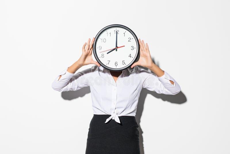 Фото смешной женщины в белой рубашке и черной стороны заволакивания юбки с большими круглыми часами изолированными над белой пред стоковое изображение