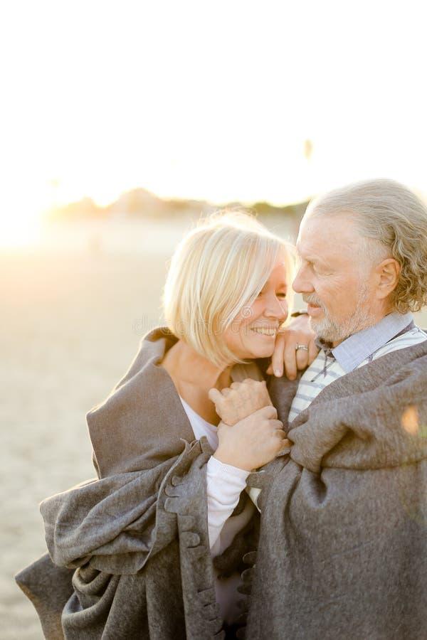 Фото солнечности старшего супруга обнимая шотландку жены нося на пляже песка стоковое фото