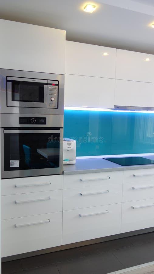 Фото средней квартиры кухни размера в цветах бирюзы, кожаного современного и минималистского seater, белого обеденного стола для  стоковая фотография