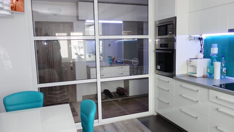 Фото средней квартиры кухни размера в цветах бирюзы, кожаного современного и минималистского seater, белого обеденного стола для  стоковые фотографии rf
