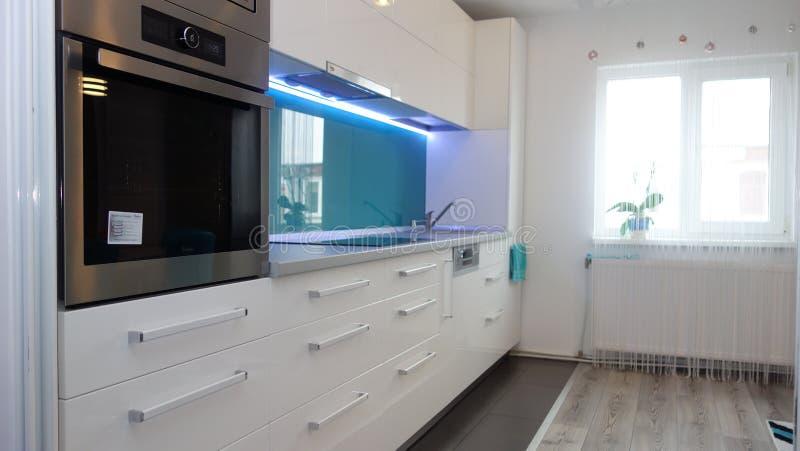 Фото средней квартиры кухни размера в цветах бирюзы, кожаного современного и минималистского seater, белого обеденного стола для  стоковое изображение