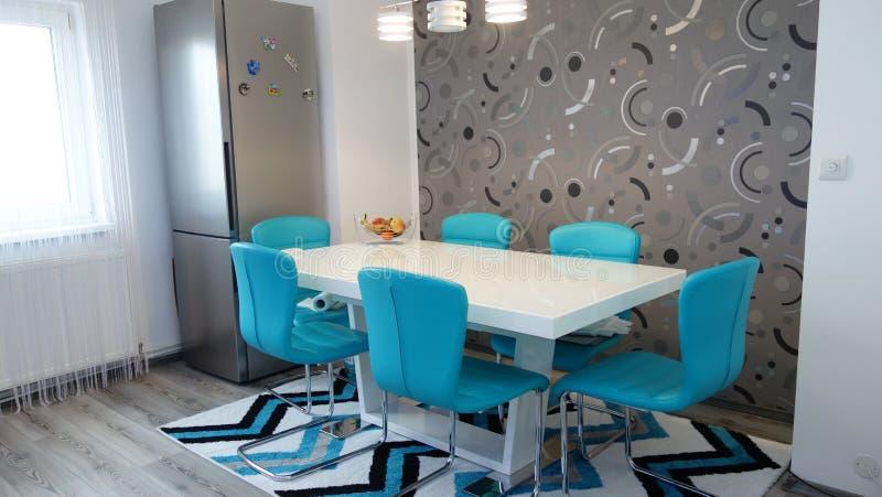 Фото средней квартиры кухни размера в цветах бирюзы, кожаного современного и минималистского seater, белого обеденного стола для  стоковое фото rf