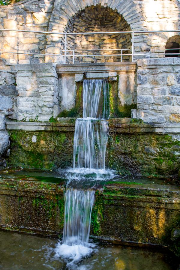 Фото старого маленького водопада фонтана в парке стоковые изображения