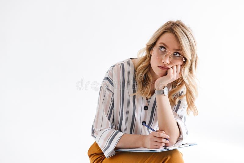Фото стекел белокурой серьезной женщины нося подпирая ее голову и выглядя верхний пока сидящ стоковые изображения
