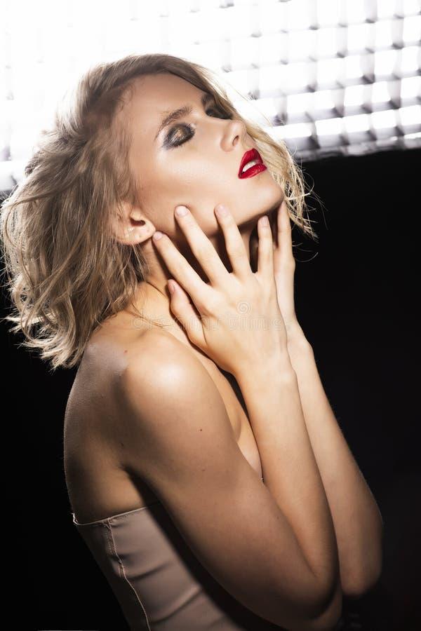 Фото стиля искусства и моды красивой девушки с disheveled влажными волосами, нагими плечами, красными губами, касается ее стороне стоковое фото rf