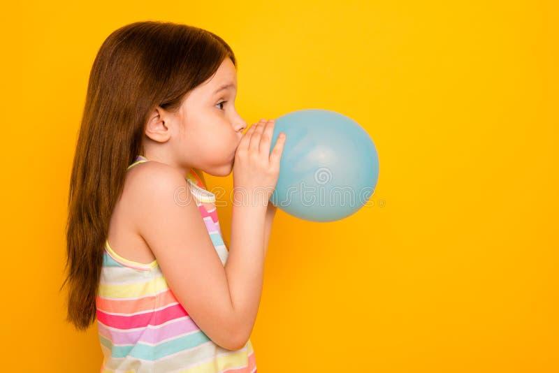 Фото стороны профиля очаровательного ребенк надувая baloon изолированное над желтой предпосылкой стоковое фото