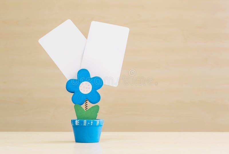 Фото струбцины крупного плана в голубой форме формы цветка в цветочном горшке с черной белой бумагой на запачканной деревянной пр стоковые фото