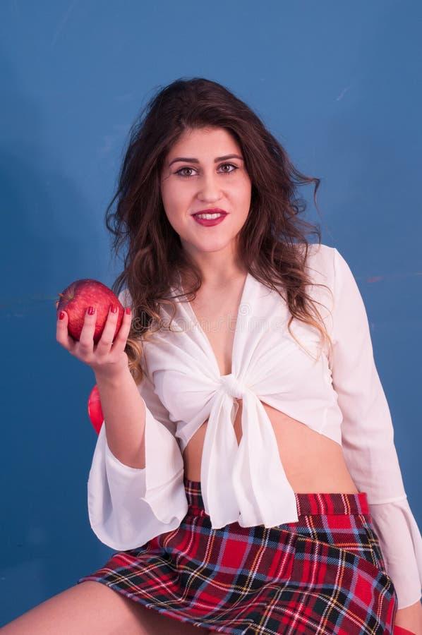 Фото студии с милой девушкой и яблоком стоковое изображение rf