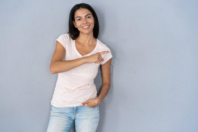 Фото счастливого положения молодой женщины изолированное над серой предпосылкой стены Смотреть камеру показывая указывать copyspa стоковая фотография rf
