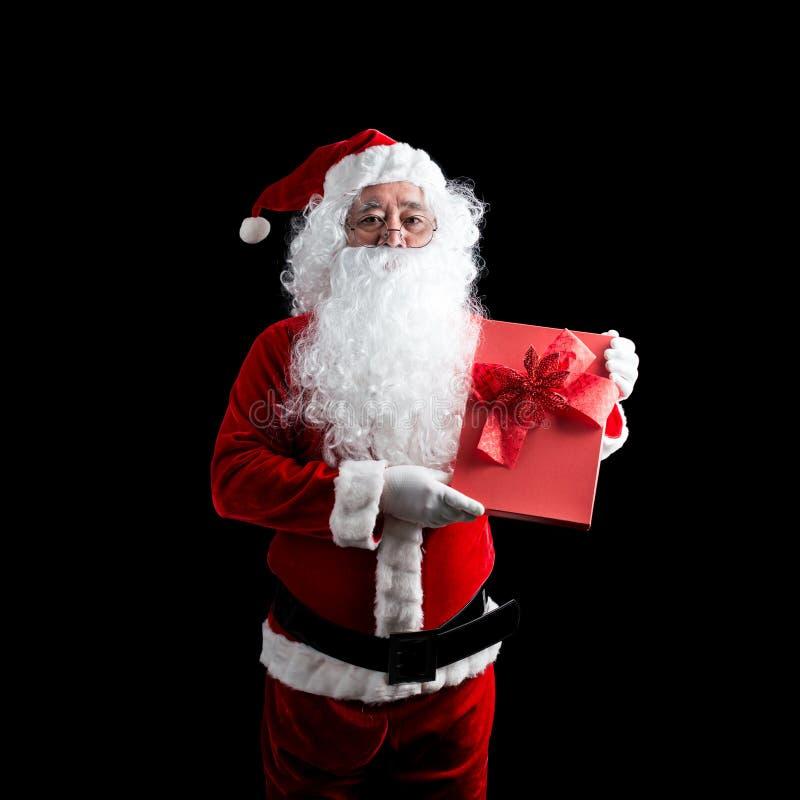 Фото счастливого Санта Клауса при красная подарочная коробка подарка на рождество в руках, изолированная на черной предпосылке стоковое изображение
