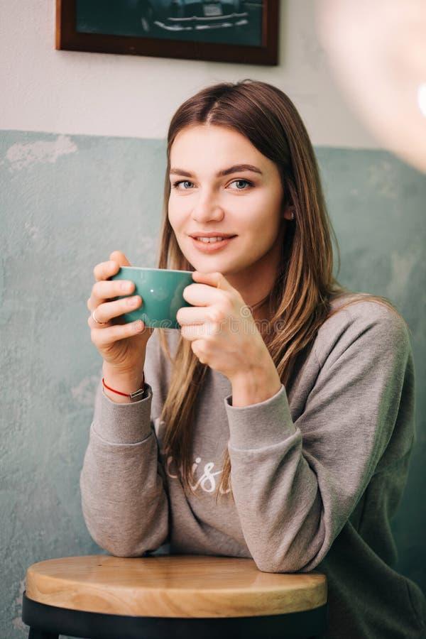 Фото счастливой блондинкы с чашкой кофе в руке стоковая фотография