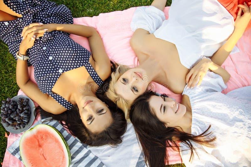 Фото 3 счастливых девушек лежа на зеленой траве и усмехаться стоковая фотография