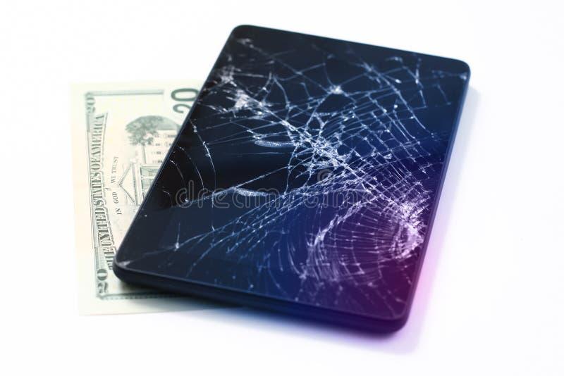 Фото треснутого дисплея на планшете и 20 долларах изолированных на белизне Планшет с поврежденным экраном стоковая фотография