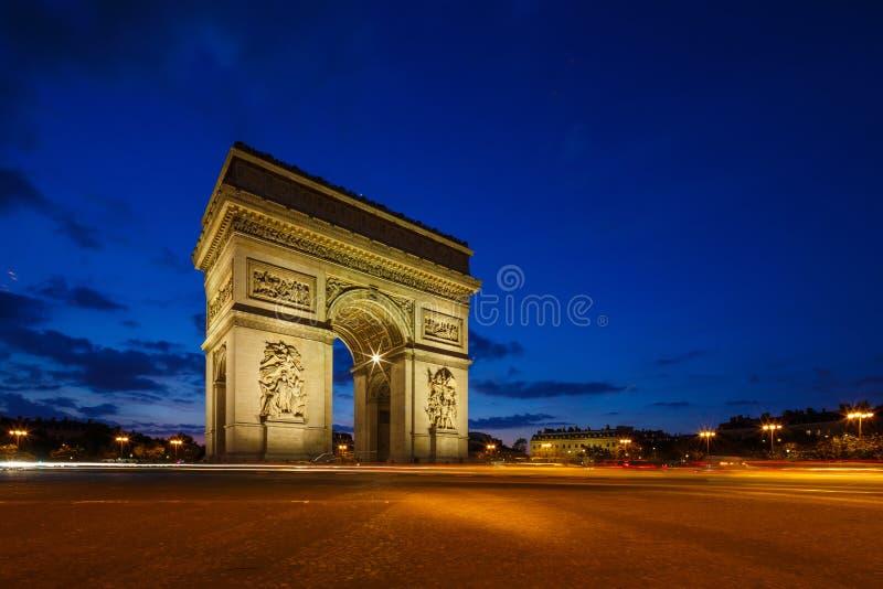 Фото Триумфальной Арки twilight, бульвар de Champs-Elysees, Париж стоковая фотография rf