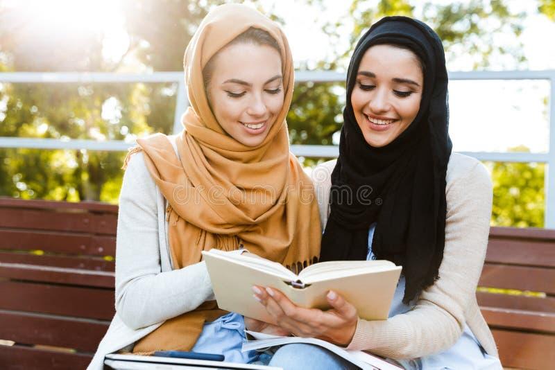 Фото умных исламских девушек нося headscarfs сидя в зеленом парке стоковое изображение