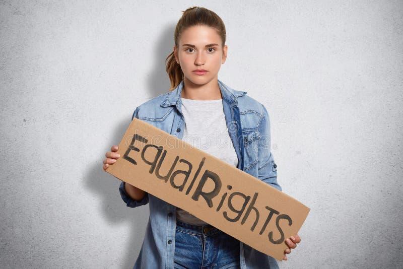 Фото феминиста в куртке джинсовой ткани, владениях подписывает написанные равные права, показывает что женщины имеют права и силу стоковая фотография rf