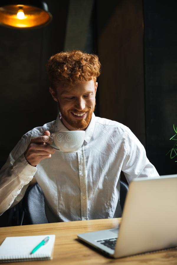 Фото человека детенышей усмехаясь readhear бородатого держа чашку coffe, l стоковое изображение rf