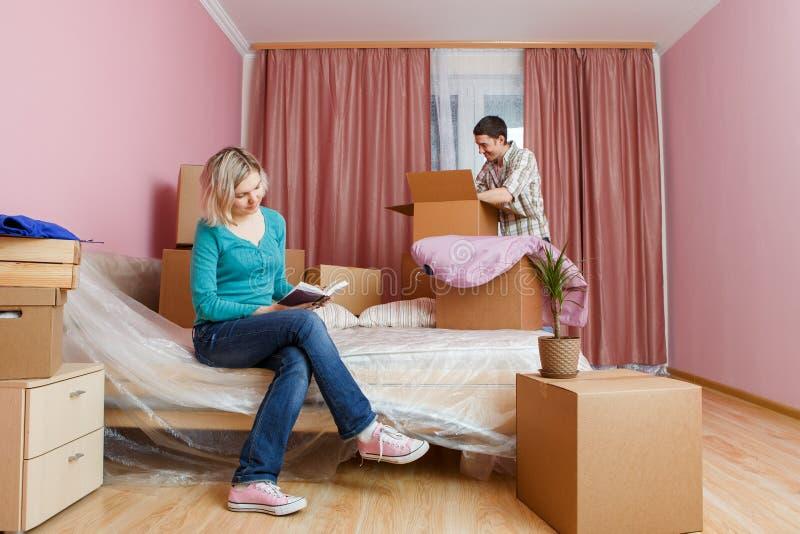 Фото человека и женщины при книга сидя на кровати среди картонных коробок стоковая фотография
