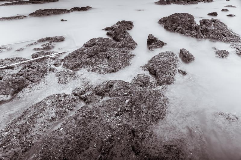 Фото черно-белое волн фотографии долгой выдержки на каменных водах пляжа окаймляет абстрактную предпосылку моря r стоковое фото rf