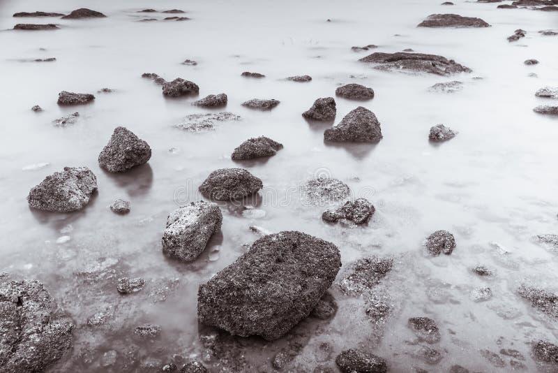 Фото черно-белое волн фотографии долгой выдержки на каменных водах пляжа окаймляет абстрактную предпосылку моря r стоковое изображение rf
