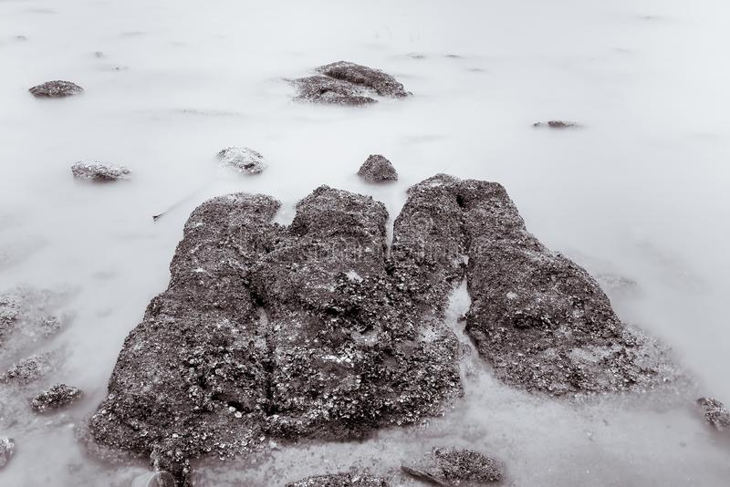 Фото черно-белое волн фотографии долгой выдержки на каменных водах пляжа окаймляет абстрактную предпосылку моря r стоковые изображения