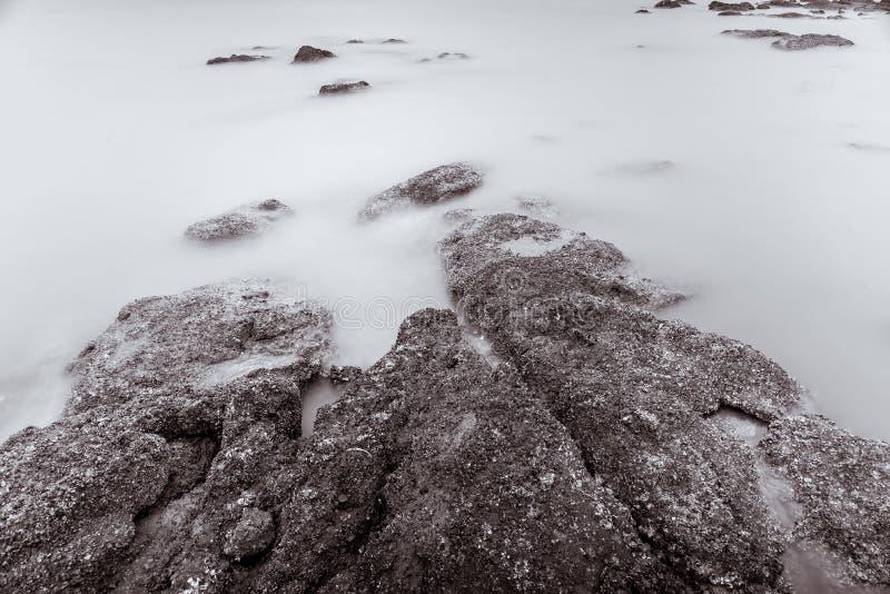 Фото черно-белое волн фотографии долгой выдержки на каменных водах пляжа окаймляет абстрактную предпосылку моря r стоковые изображения rf