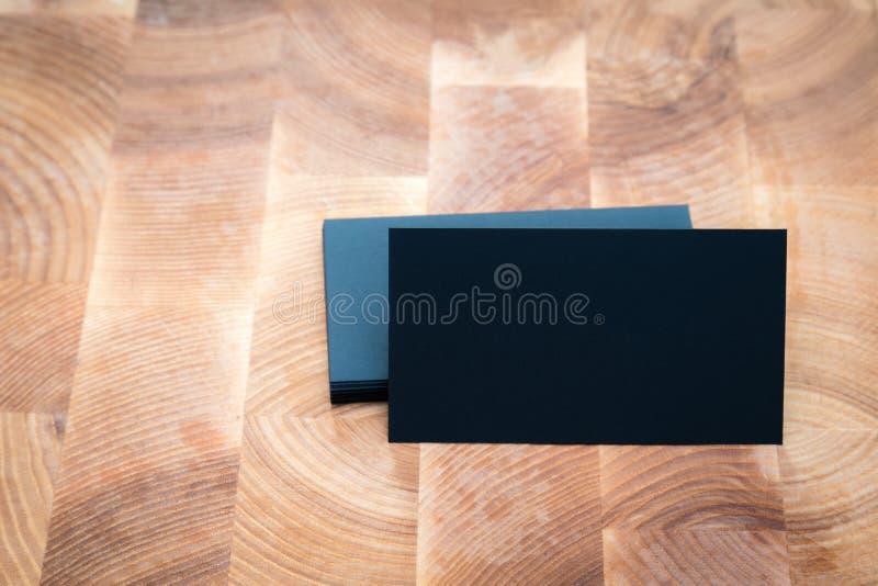 Фото черных пустых визитных карточек на деревянной предпосылке Templa стоковые фотографии rf