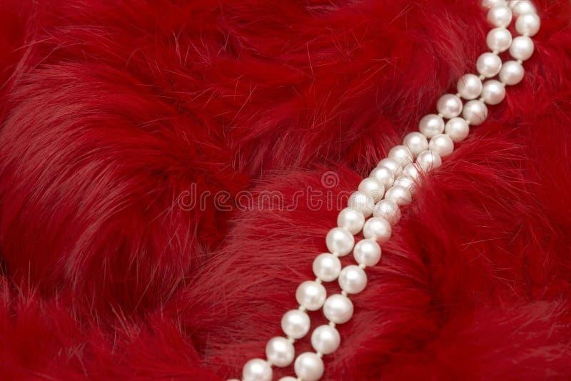 Фото элегантного ожерелья жемчуга на глубоком - красное мех Селективный мягкий фокус Концепция красоты моды очарования женщины Ме стоковое изображение