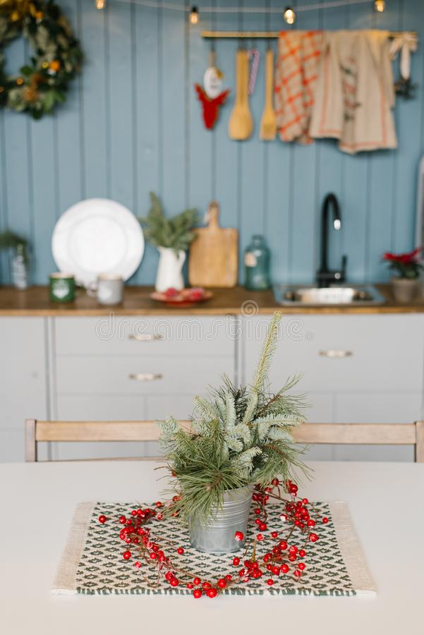 Фрагменты ели или сосны в металлическом декоративном ведре на кухонном столе, украшенные на Рождество стоковые фотографии rf