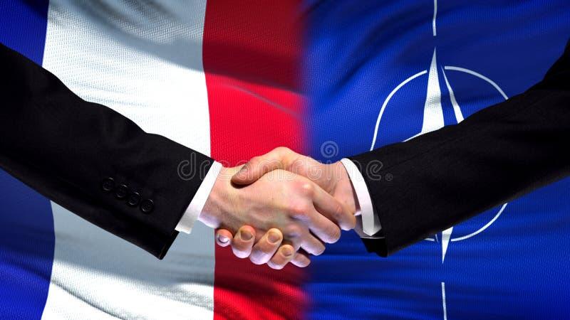 Франция и рукопожатие НАТО, международные отношения приятельства, предпосылка флага стоковая фотография rf