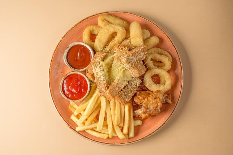 Французские фраи, кольца лука, крыла цыпленка, сухари, закуска к пиву на большой плите с 2 соусами на коричневой предпосылке Взгл стоковые изображения rf