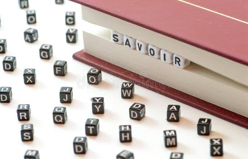 Французский знать смысла savoir слова написанный при письма поглощенные между книгой хранит и письмами распространения на белом c стоковое фото rf