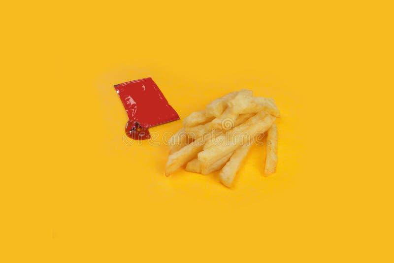 Французский картофель фри и красный конверт томатного соуса на желтой предпосылке стоковые изображения rf