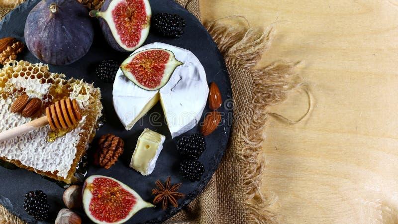 Французский мягкий Camembert сыр, оригинальный Camembert de Normandie подается с свежими спелыми инжирами, близкими Верхнее предс стоковое изображение rf