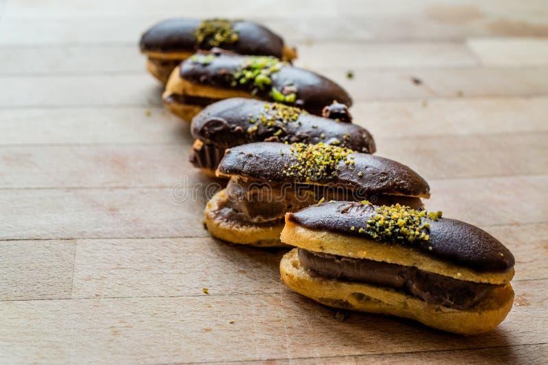 Французский порошок заполненный Eclairs шоколада десерта со сливками и фисташка/Profiteroles стоковое изображение