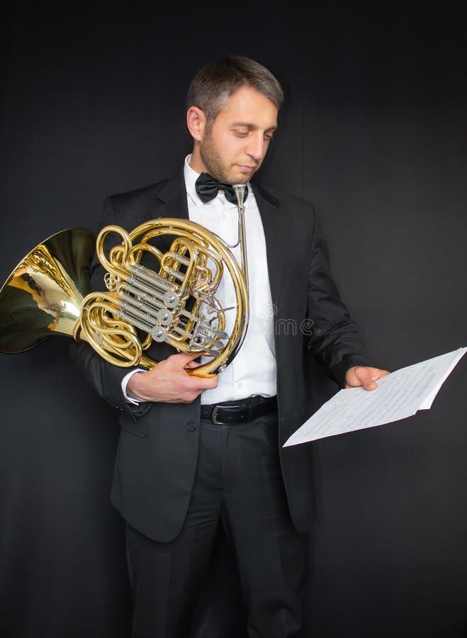 французский рожочок Ручка музыкального инструмента в руках rogant Человек в костюме и бабочка с музыкальным инструментом стоковые изображения