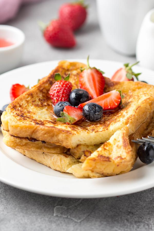 Французский тост с ягодами (голубиками, клубниками) и соусом, традиционным сладким десертом хлеба с яйцом и молоком E стоковые изображения rf