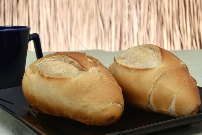 Французский хлеб, на плите с черной чашкой в предпосылке стоковые фото