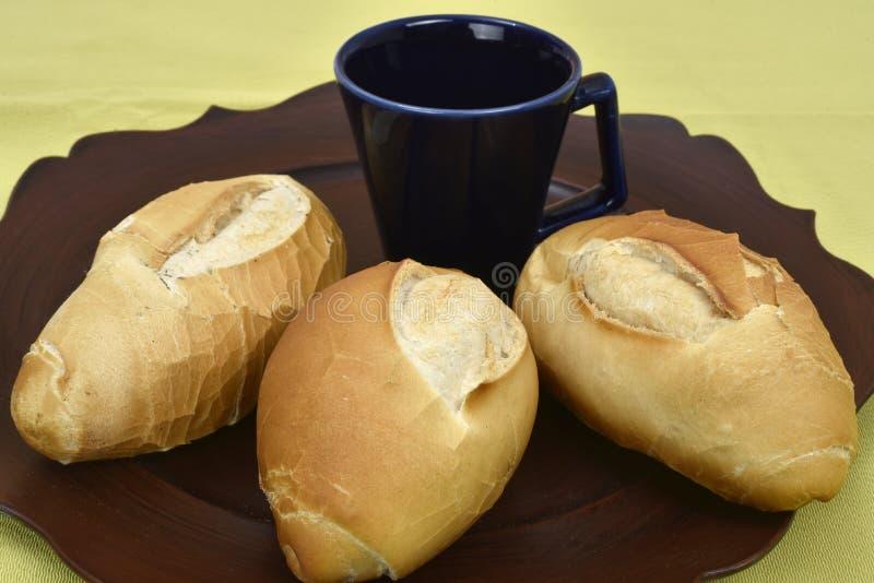 Французский хлеб на плите с черной чашкой на заднем плане стоковые изображения