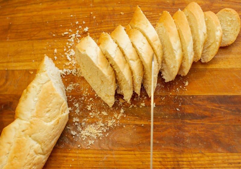 Французский хрустящий свежий багет с золотой коркой или длинным хлебцем испеченными в пекарне и отрезок в куски на деревянной дос стоковые фото