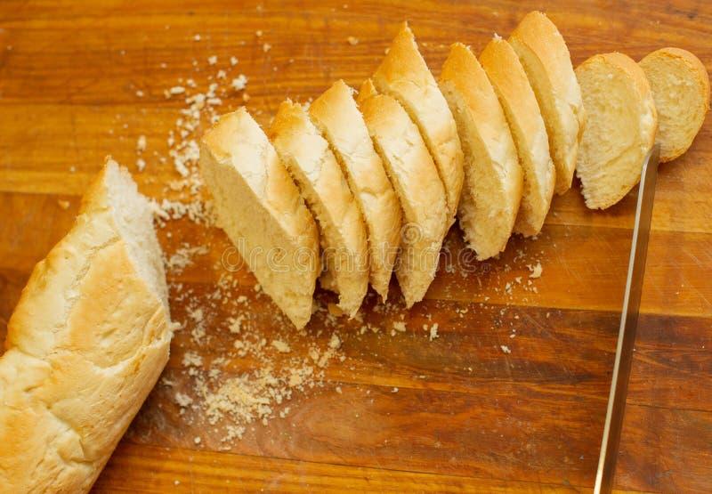 Французский хрустящий свежий багет с золотой коркой или длинным хлебцем испеченными в пекарне и отрезок в куски на деревянной дос стоковое фото rf