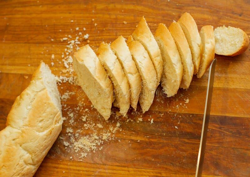 Французский хрустящий свежий багет с золотой коркой или длинным хлебцем испеченными в пекарне и отрезок в куски на деревянной дос стоковое изображение
