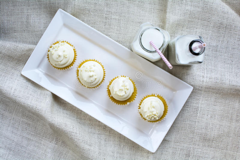 4 французских ванильных пирожные и молока в бутылочном стекле стоковое фото