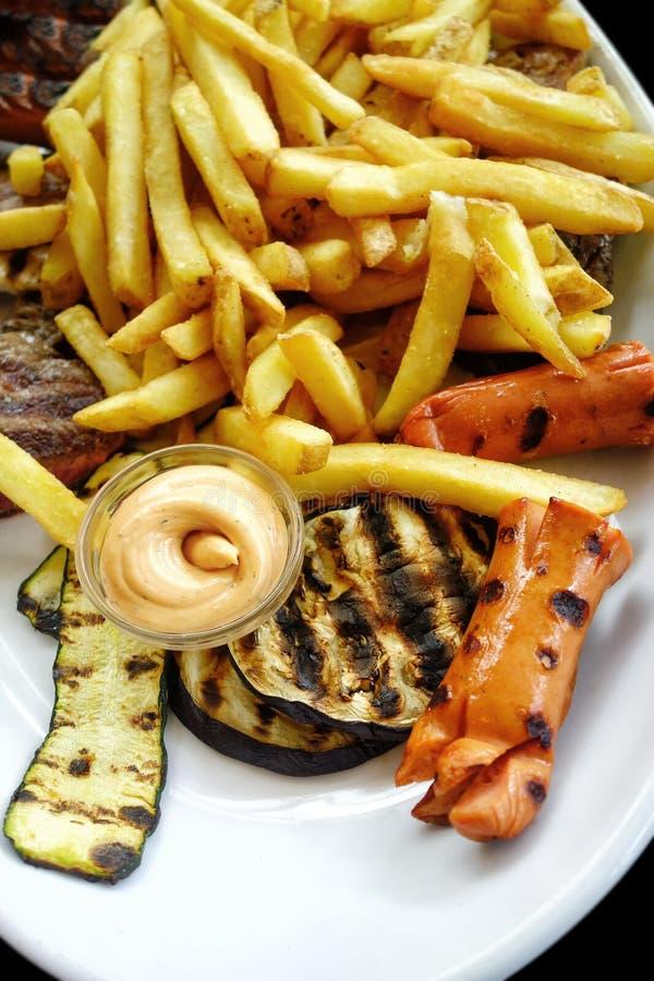 Француз горячей сосиски жарит овощи и мясо на плите стоковое изображение