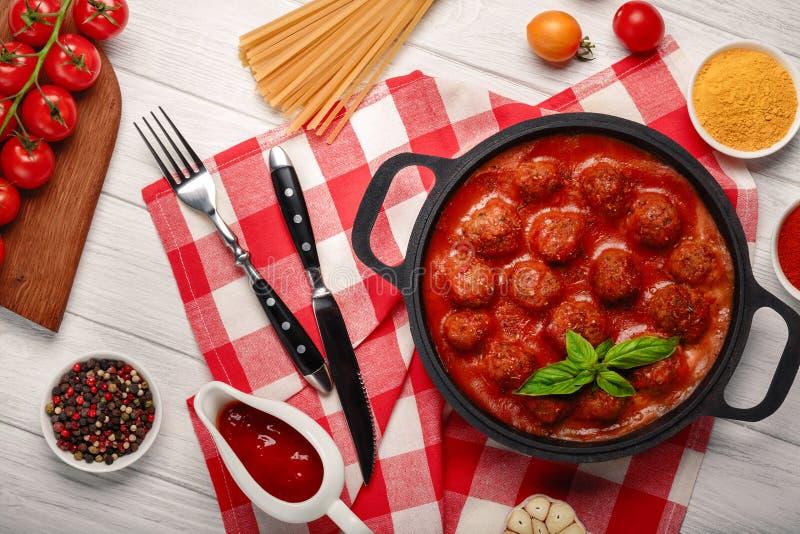 Фрикадельки в томатном соусе со специями в сковороде и томатах вишни на разделочной доске и белой деревянной доске стоковое фото rf