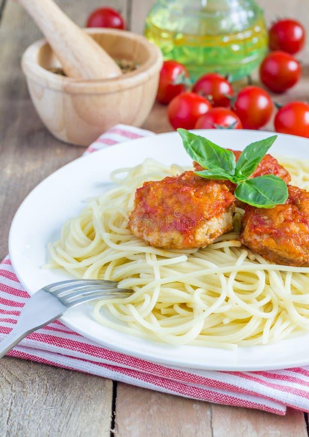 Фрикадельки в томатном соусе с спагетти на белой плите стоковая фотография rf